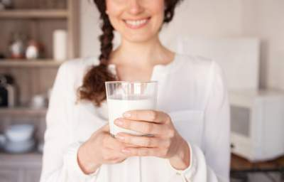 a lady holding a glass of milk